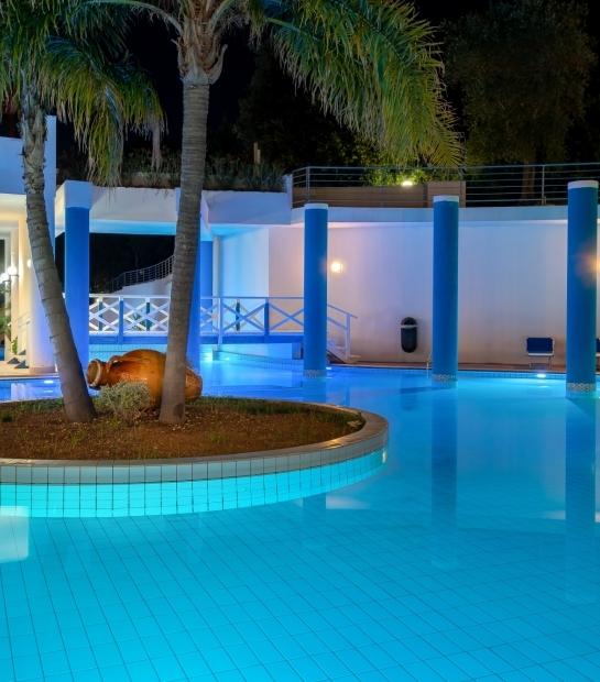 Anfora decorativa e palme al centro della piscina